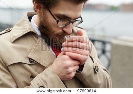 Elegant young man lighting cigarette outdoors