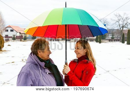 Happy elderly woman and young caregiver walking in the park with colorful umbrella