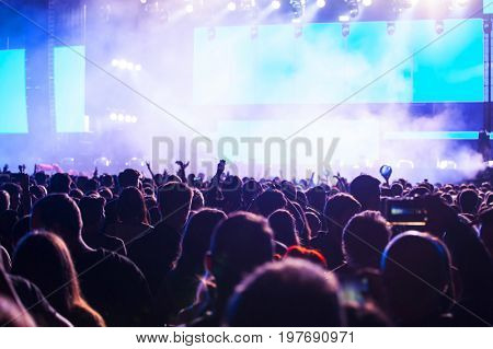 Crowd at concert - Cheering crowd in front of bright colorful stage lights