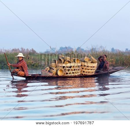 NYAUNG SHWE, MYANMAR - JANUARY 12, 2012: Intha women with manufactured goods sailing in wooden boat to weekly market on Inle Lake, Shan State.