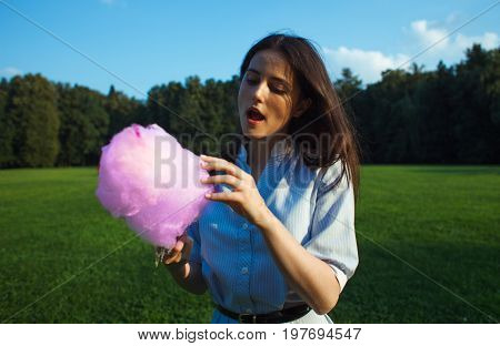 young pretty brunnette woman eating pink cotton candy outdoor on nature park