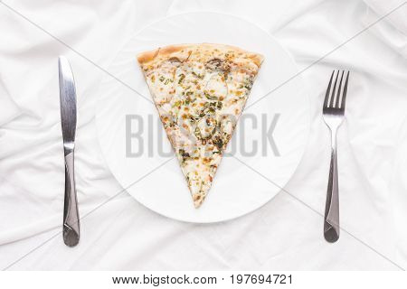 Piece of pizza on a plate fork and knife on a white tablecloth