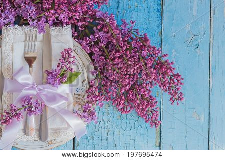 Tableware And Silverware With Bunches Of Violet Lilac On The Wooden Background
