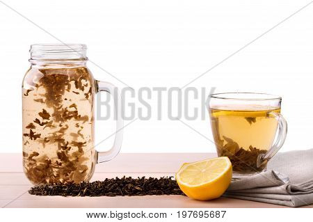 A sweet black tea and a cut lemon isolated on a white background. Organic Chinese tea in a big mason jar and a transparent cup with a hot drink. Herbal tea leaves and a lemon on a fabric on a table.