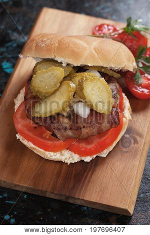 Bacon burger sandwich with tomato, onion and pickles