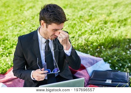 Tired employee touching bridge of his nose while working outdoors