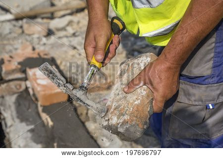 Builder Hands With Old Clay Brick And Hammer