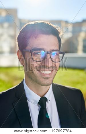 Handsome man in formalwear and eyeglasses looking at camera