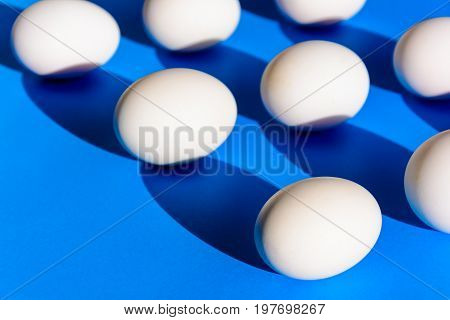 Raw duck eggs white and shiny black on blue paper with minimal and easter