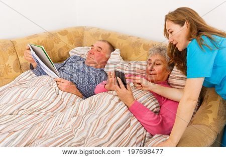 Senior man reading and his wife learning to use the smartphone with the young carer