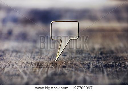 Tweet or remark. Blank speech bubble made of gold wire on rustic or grunge wood ready for inserting text. Muted tone. Shallow depth of field.