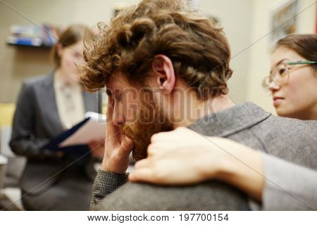 Portrait of young man crying in couples counseling session with  wife hugging him supportively