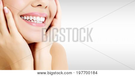 Closeup shot of happily laughing pretty woman against a grey background with copyspace