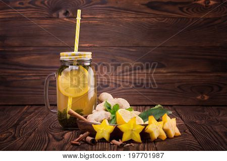 A refreshing green tea with lemon in a mason jar with a straw and a cut yellow carambola. A bowl full of ginger, cinnamon sticks, lemon slices and green mint leaves on a dark brown wooden background.