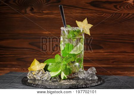 A glass of alcoholic lime mojito on a dark brown wooden background. A cold mojito with rum and liquor on a black plate. Mint leaves, crushed ice and yellow carambola. Alcohol for parties. Copy space.