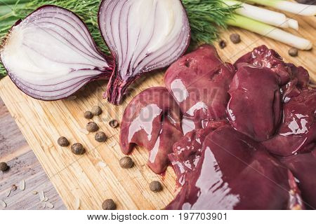 Fresh chicken liver onion pepper on a wooden cutting board