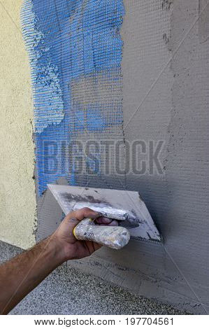 Spreading Mortar On Mesh Of Styrofoam Insulation Wall