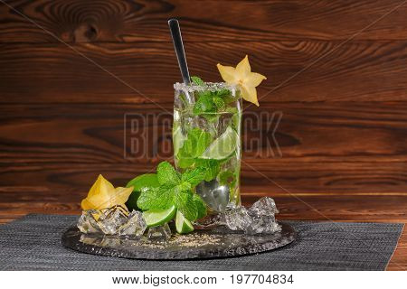 A glass of alcoholic lime mojito on a light wooden background. A cold mojito with rum and liquor on a black plate. Mint leaves, crushed ice and yellow carambola. Alcohol for parties. Copy space.