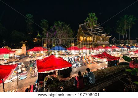 LUANG PRABANG LAOS - MARCH 11 2017: From the top wide angle picture of Haw Pha Bang and Night Market located on the grounds of the Royal Palace Museum in Luang Prabang Laos.