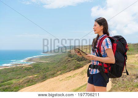 Female Backpacker Holding Online Travel Guidebook