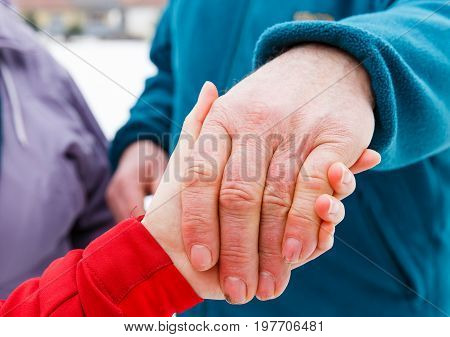 Close up photo of young caregiver holding elderly man hand
