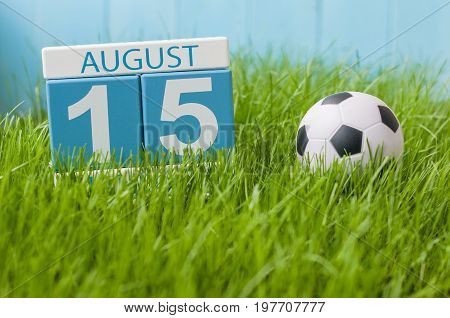 August 15th. Image of august 15 wooden color calendar on green grass lawn background with soccer ball. Summer day. Empty space for text.