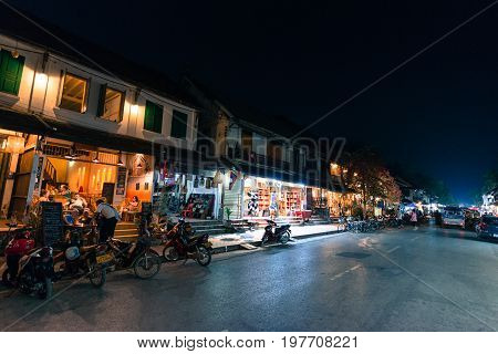 LUANG PRABANG LAOS - MARCH 11 2017: Night shoot of coffee shops restaurants and stores at Sisavangvong Road located in the olf Quarter of Luang Prabang Laos.