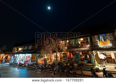 LUANG PRABANG LAOS - MARCH 11 2017: Night shoot over the moonlight of coffee shops and restaurants at Sisavangvong Road located in the olf Quarter of Luang Prabang Laos.