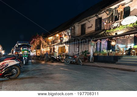 LUANG PRABANG LAOS - MARCH 11 2017: Long exposition picture of coffee shops restaurants and tuk tuk at Sisavangvong Road located in the olf Quarter of Luang Prabang Laos.