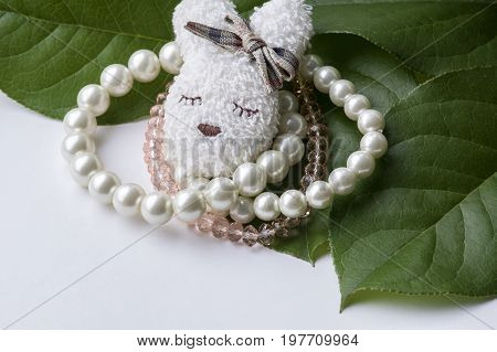 Several white and pink bracelets with brooch on the green leaves and white background