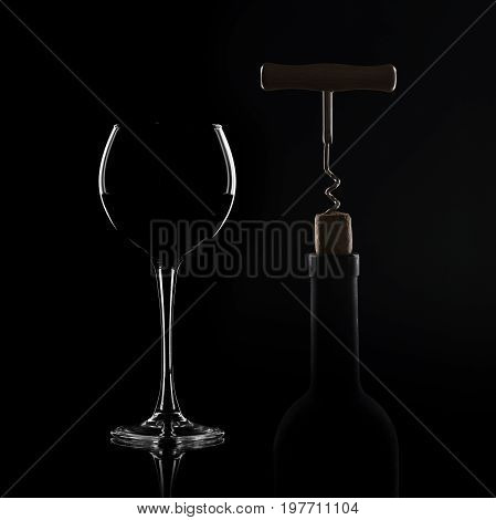 Red wine pouring in wineglass from bottle over black background. Wine list design menu with copyspace. Alcohol beverage card backdrop