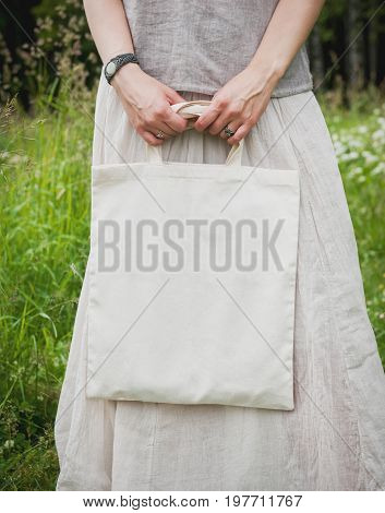 Woman holding empty linen bag outdoor. Template mock up