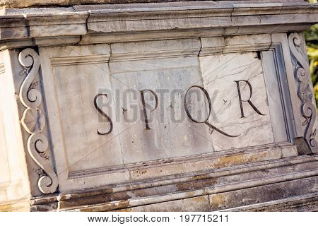 SPQR is Senatus Populusque Romanus, official emblem of modern-day Rome and classic symbol of Ancient Rome, phrase found all over city, imprinted beneath statue near Campidoglio and Colosseum.