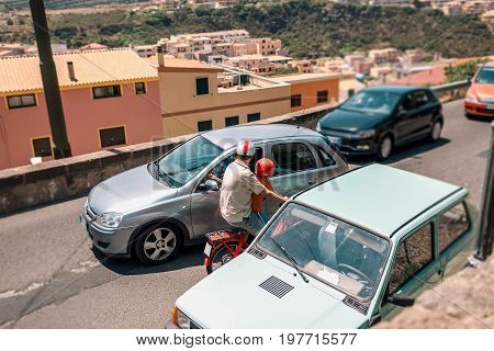 Man With Child On Moped Between Cars In Italian Street. Sardinia. Italy.