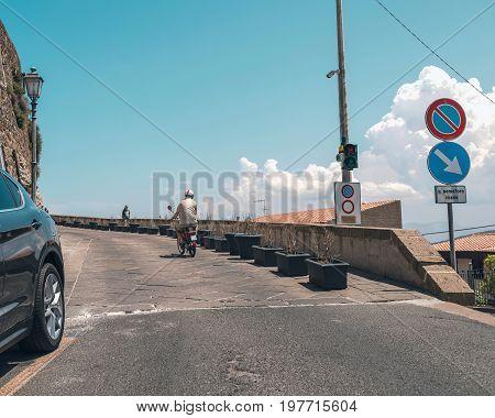 Man On Moped In Street Of Italian Town. Sardinia. Italy.