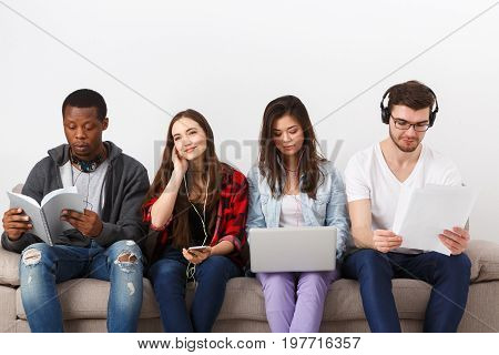 Modern education. Young diverse students, people listen to music with gadgets, sitting together on couch indoors