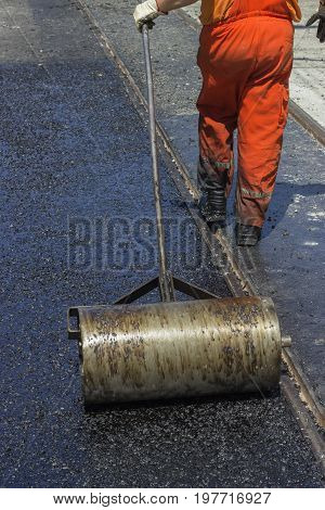 Worker Using A Hand Roller For Mastic Asphalt Paving