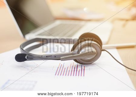 close up earphone of call center lay on paperwork with laptop computer on desktop,helpdesk receiver job concept
