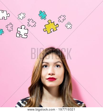 Puzzle with young woman on a pink background