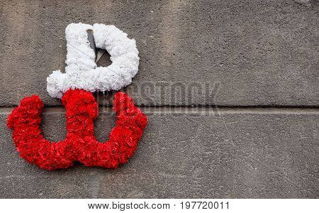 kotwica - the emblem of the Polish resistance against German occupation, made of flowers on a concrete wall. It also stands for the memory of the Warsaw Uprising which started August 1st 1944.