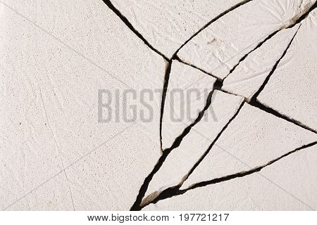 Fractured white concrete background. Old cracked plaster floor top view, copy space