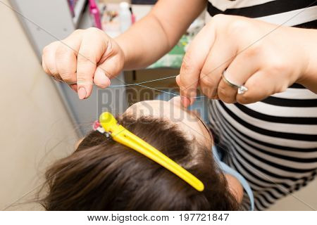 Plucking eyebrows with a woman's thread in a beauty salon