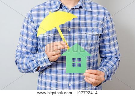 Man Holding Model Of House. Concept For Home Insurance