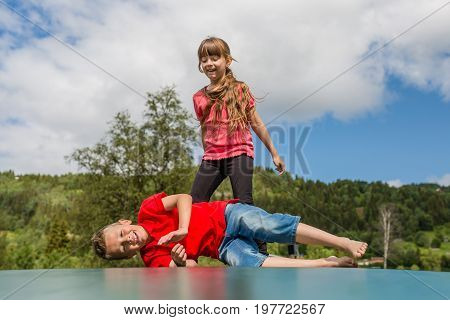 Two scandinavian kids playing and having fun while jumping on large inflatable bouncing pillow.