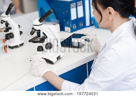 Modern equipment. Nice smart intelligent woman sitting at the table and holding a sample slide while working with a microscope