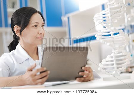 Human body. Positive nice smart scientist looking at the gene model and holding a tablet while studying genome