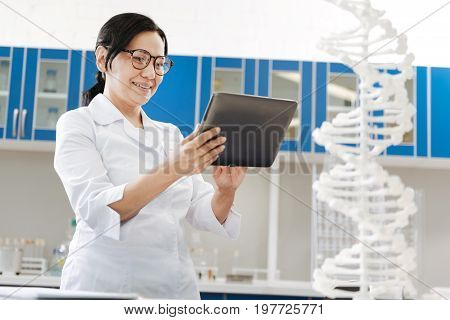 Genetic researcher. Delighted smart good looking woman standing in the lab and using a tablet while doing her job as a genetic researcher