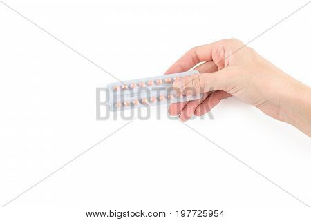 Birth control pills or pregnancy prevention pills of full package in female or woman right hand isolated on white background with copy space for text insertion or decoration (clipping path included) lady health care concept