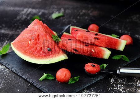 watermelon on a black chopping Board with mint leaves