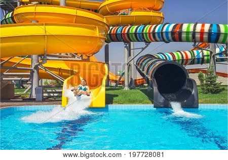Girls go down from water slide to swimming pool in aqua park.
